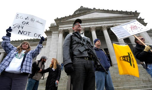 (AP Photo/Ted S. Warren, File). FILE - In this Jan. 15, 2015 file photo, Mark Ramirez, center, of Bainbridge Island, Wash., wearing his Colt M4 gun, and others participate in a gun-rights rally at the Capitol in Olympia, Wash.