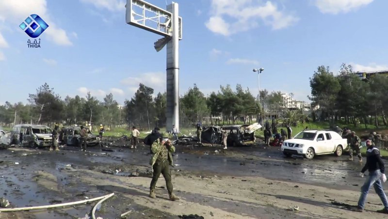 This frame grab from video provided by the Thiqa News Agency shows rebel gunmen gathered at the site of a blast that damaged several buses and vans at the Rashideen area a rebel-controlled district outside Aleppo city Syria