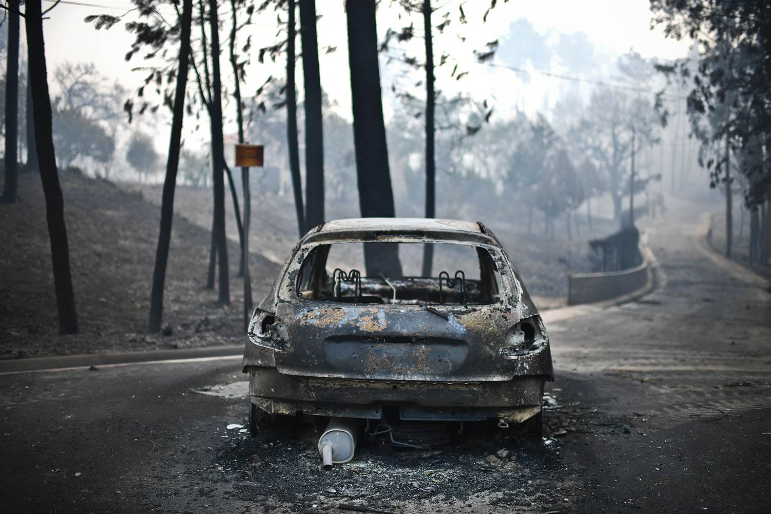 A burnt car on a road after a wildfire in Pedrogao, in central Portugal. PATRICIA DE MELO MOREIRA / AFP - Getty Images