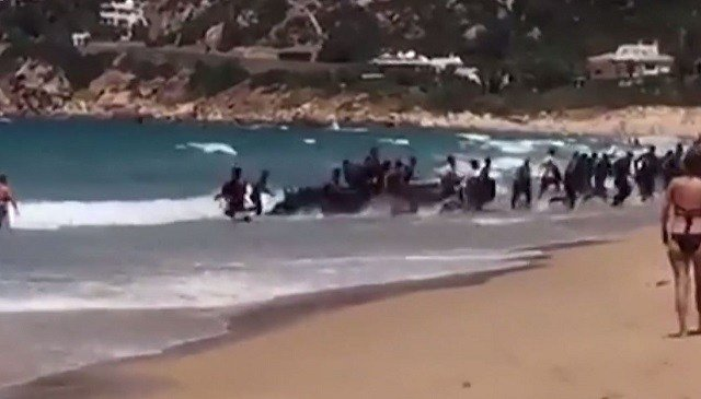 Migrants surprise sunbathers by rushing onto Spanish beach