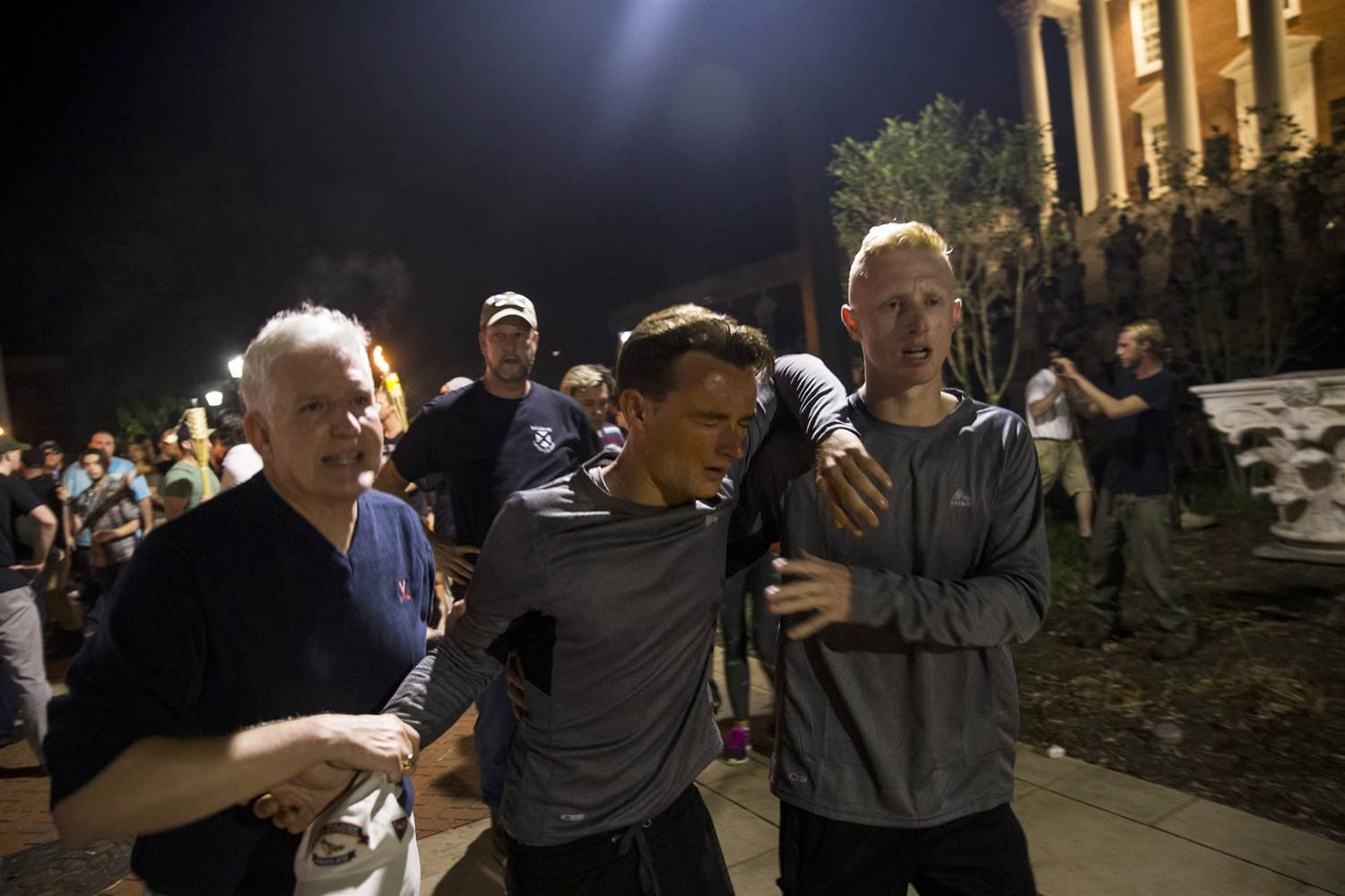 A man is helped after being hit in the face with pepper spray during a clash between counter protesters and Neo Nazis, Alt-Right, and White Supremacist groups after they marched through the University of Virginia Campus on Aug. 11, 2017.