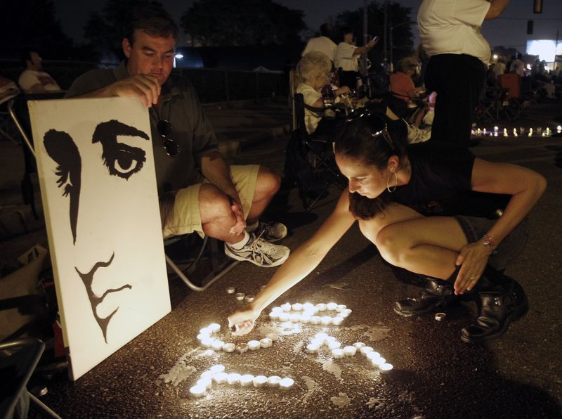 FILE- This Aug. 15, 2010 file photo shows Melanie Curry as she lights candles at an Elvis Presley display she made with Judd Cannon, left, on Elvis Presley Boulevard in front of Graceland, Presley's Memphis, Tenn. home. (AP Photo/Mark Humphrey, File)