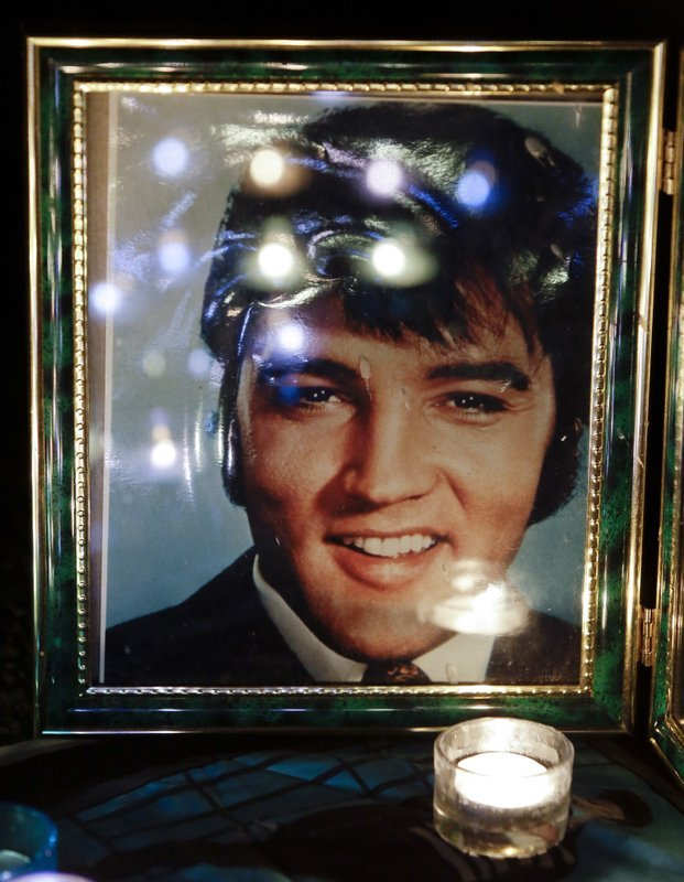 FILE- This Aug. 15, 2012 photo shows candles reflected in a photo of Elvis Presley at a memorial set up by a fan at a candlelight vigil at Graceland, Presley's Memphis, Tenn. home. (AP Photo/Mark Humphrey, File)