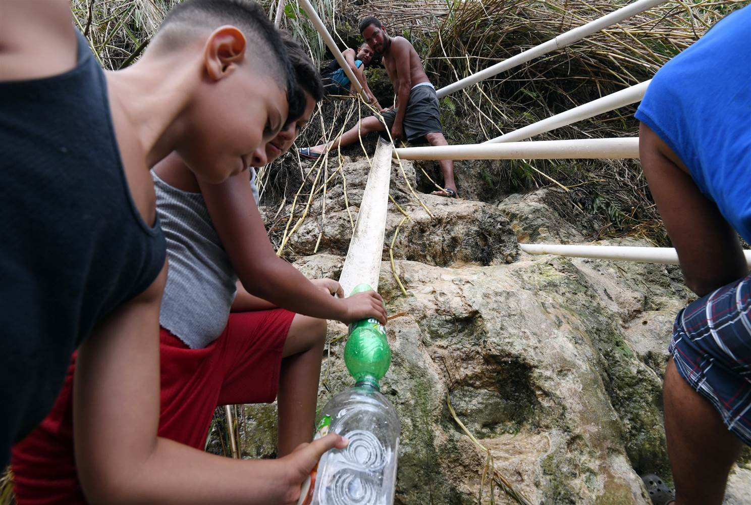 People use tubes to collect water from the mountain on September 28 in the Toa Alta and Corozal area of San Juan, Puerto Rico. (Andre Kang / GDA via AP)
