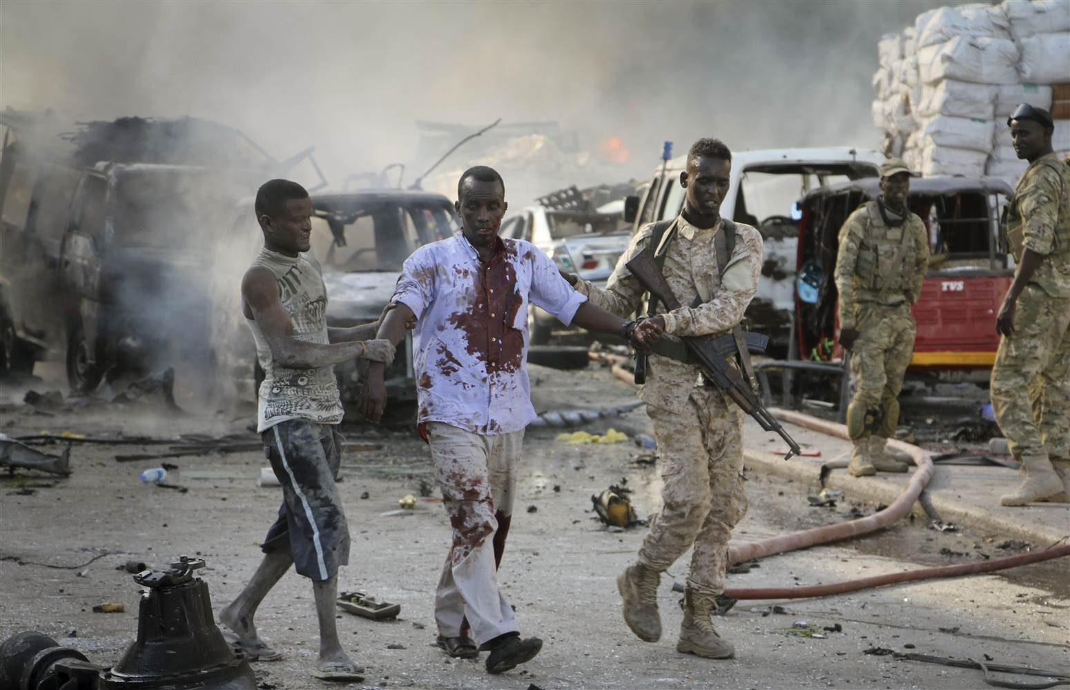Somali soldiers helps a wounded civilian from the truck blast in Mogadishu, Somalia, Saturday.