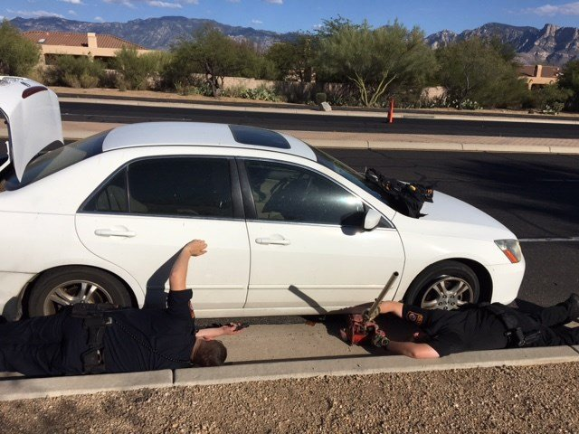 Oro Valley Police officers are installing a spare tire on Dick Bristol's, 97, car after Bristol got a flat tire.