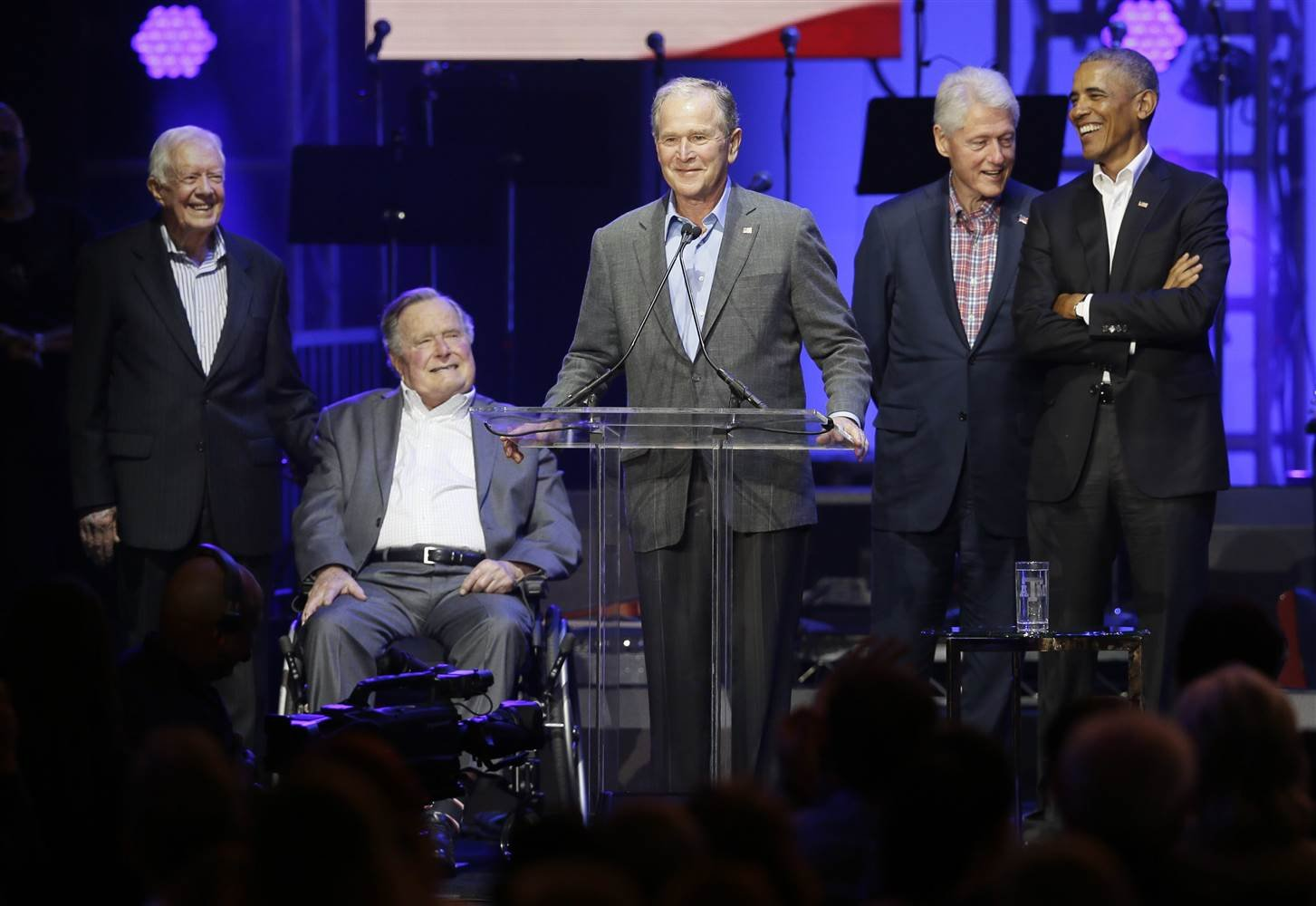 Former President George W. Bush, center, speaks as fellow former Presidents from right, Barack Obama, Bill Clinton, George H.W. Bush and Jimmy Carter look on during a hurricanes relief concert in College Station, Texas, Saturday, Oct. 21, 2017.