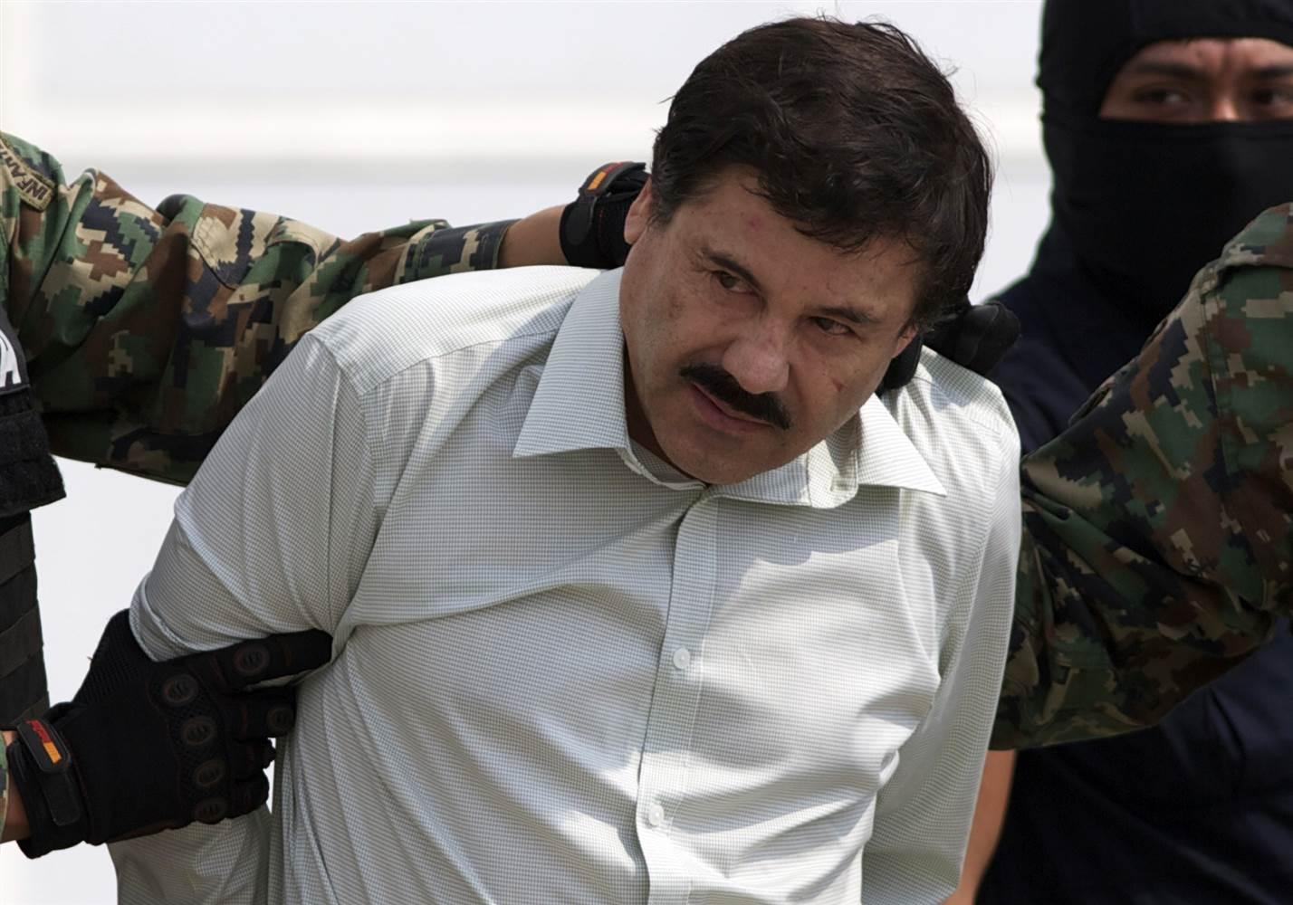 """Joaquin """"El Chapo"""" Guzman is escorted to a helicopter in handcuffs in Mexico City on Feb. 22, 2014. (Eduardo Verdugo / AP file)"""