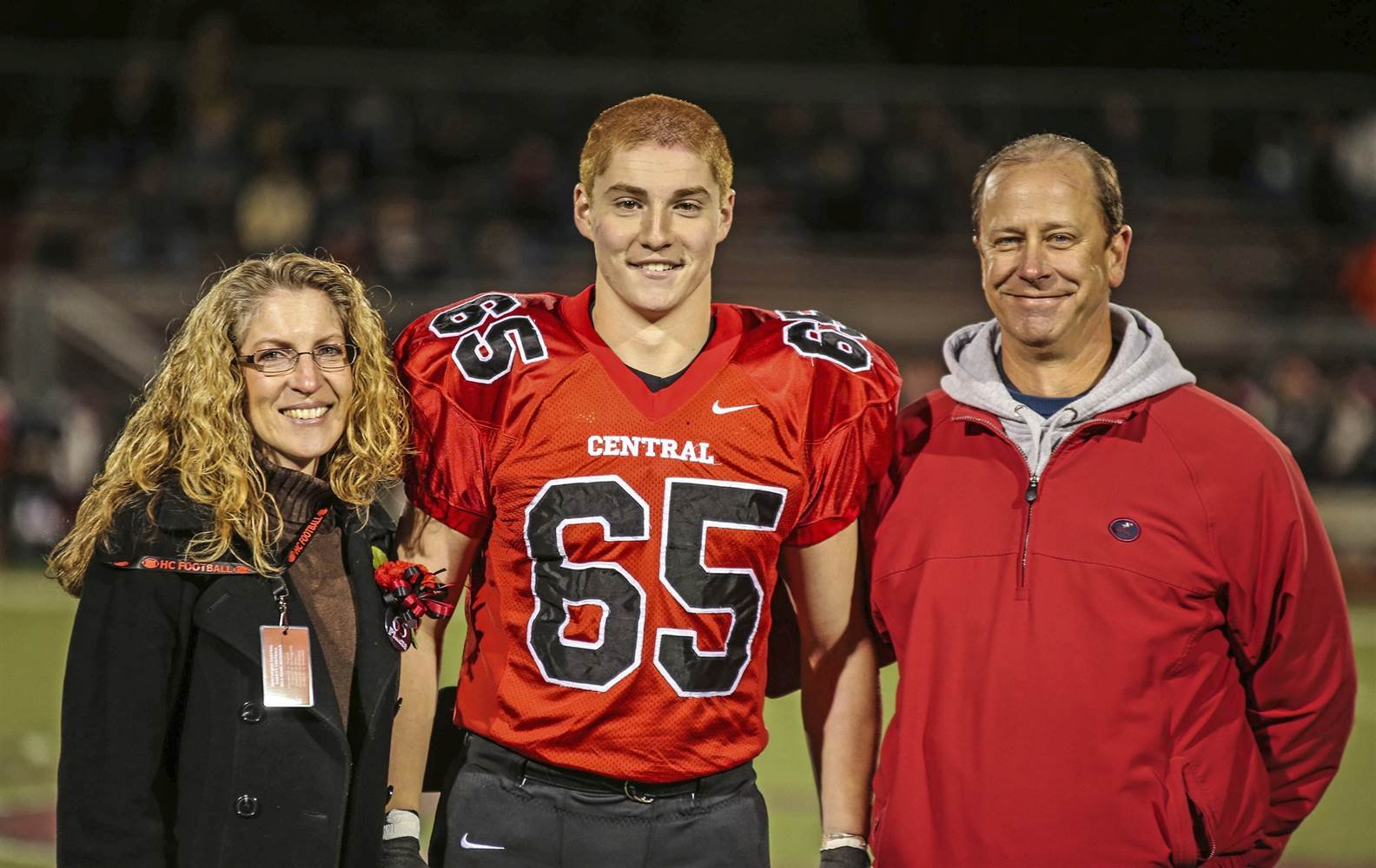 """Timothy Piazza, center, with his parents Evelyn Piazza, left, and James Piazza, right, during Hunterdon Central Regional High School football's """"Senior Night"""" at the high school's stadium in Flemington, New Jersey."""