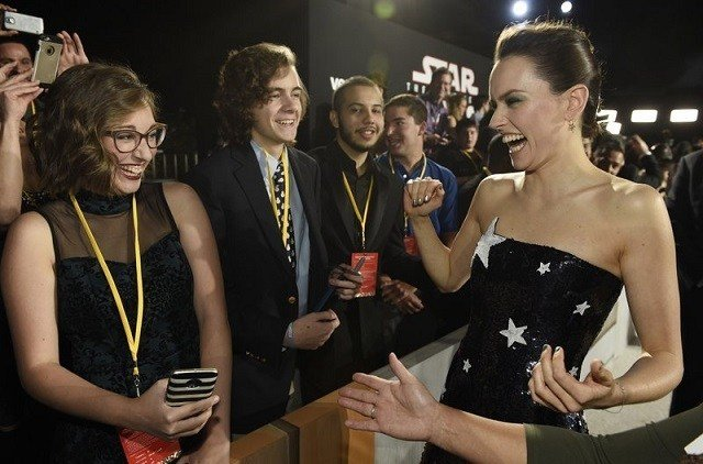 """In this Dec. 9, 2017 photo, Daisy Ridley, right, a cast member in the film """"Star Wars: The Last Jedi,"""" laughs with Shannon McNabb, from left, Tyler Woodward and Chris Alegria at the premiere of the film at the Shrine Auditorium in Los Angeles."""