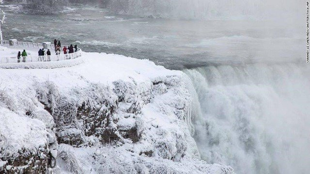 Visitors view Niagara Falls in New York on Sunday, December 31. (Source: CNN)