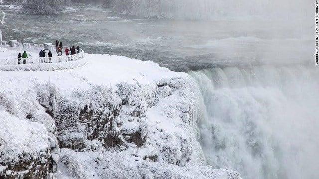 Visitors view Niagara Falls in New York on Sunday, December 31. (Source: CNN)