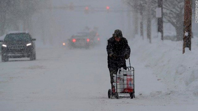 Man in Erie, Pennsylvania, walks with his groceries in a cart on December 29. (Source: CNN)