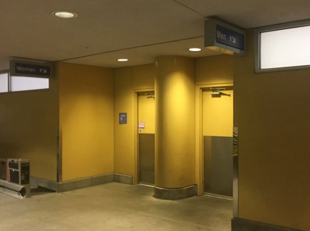 The newborn child was cleaned and wrapped up, laying on a changing table in a public restroom near the car rental center, which is outside of the security checkpoints.