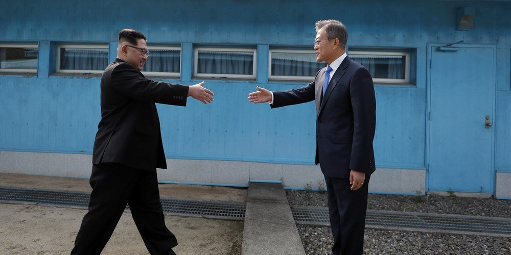 Kim Jong Un and Moon Jae-in prepare to shake hands over the military demarcation line.