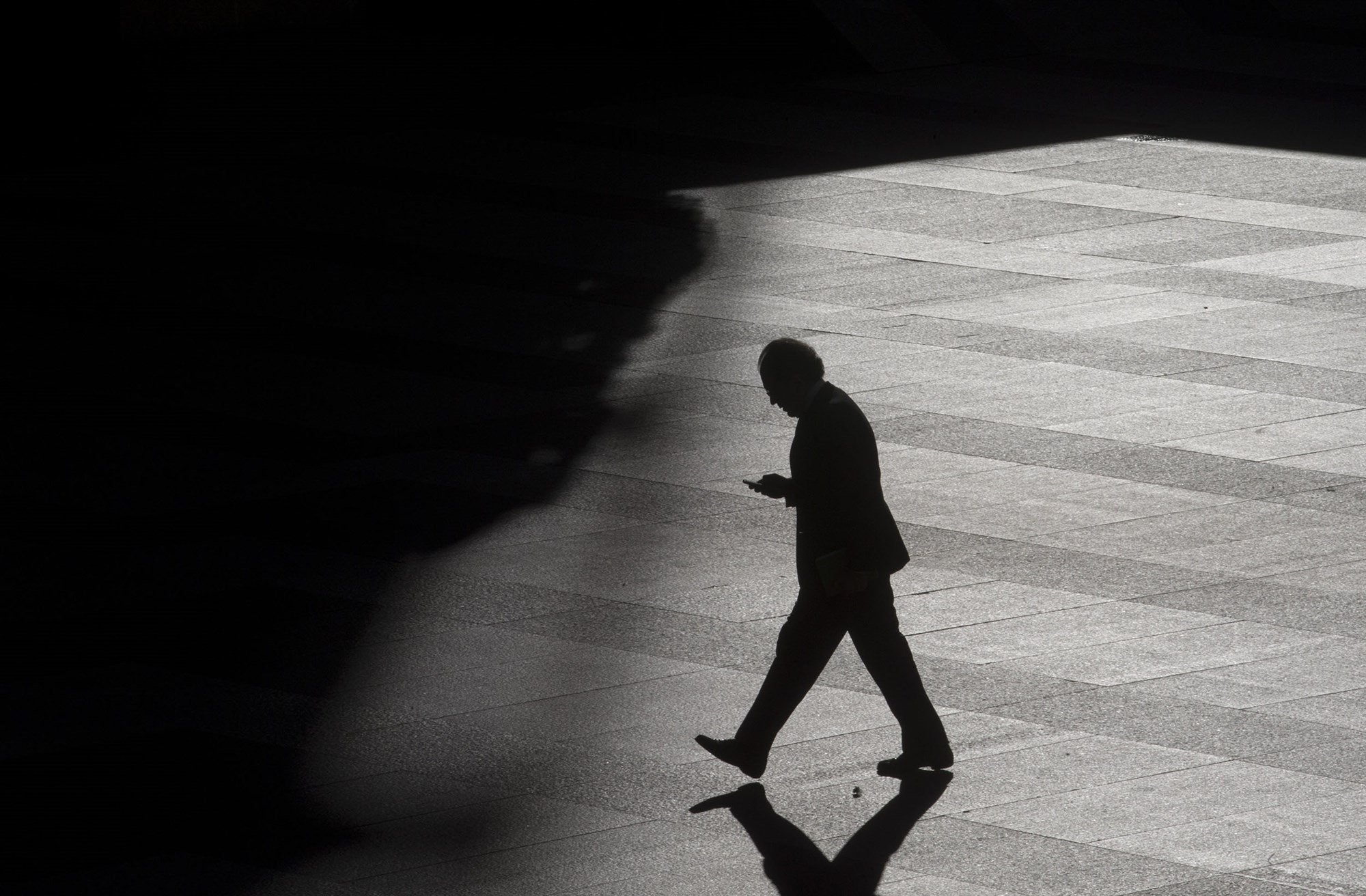 A man looks as his cell phone as he walks into the shadows in a business district. (Paul White / AP file)