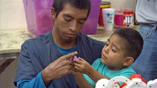A migrant father recently reunited with his son plays with modeling clay at Annunciation House in El Paso, Texas, on July 11.NBC News