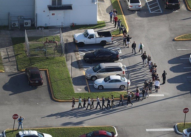 People are taken out of Marjory Stoneman Douglas High School in Parkland, Florida, after a shooting on Feb. 14, 2018.Joe Raedle / Getty Images file (Photo via NBC News)