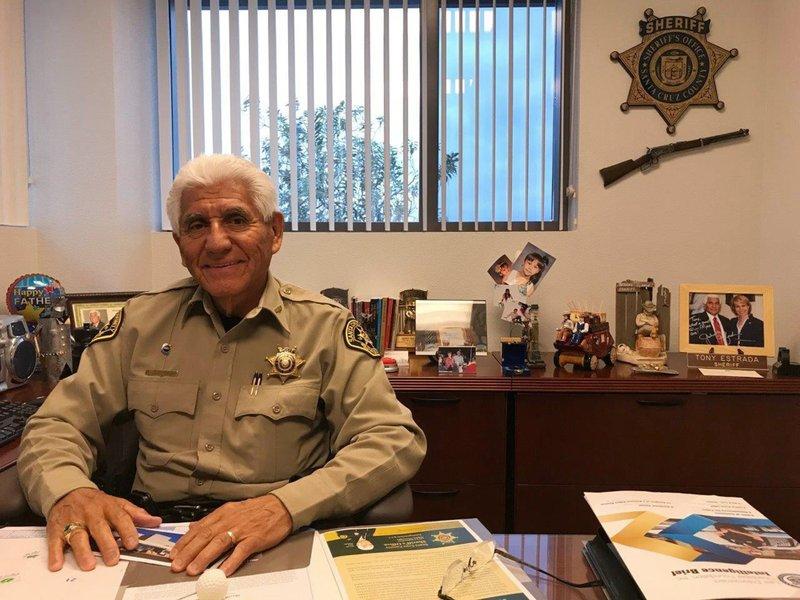 In this Dec. 5, 2017, photo, Santa Cruz County Sheriff Tony Estrada poses in his office in Nogales, Ariz.